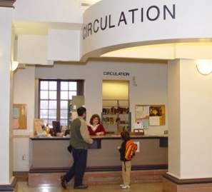 photograph of Ellis Library Circulation Desk with library users checking out materials