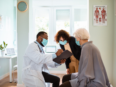 Photo of three people in a doctors office, everyone wearing masks and looking a the doctor explain something during the doctors appt