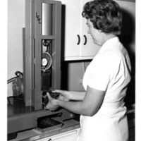 A research home economist using a shear press to measure the tenderness of meat samples cut from roasts prepared by different cooking methods.